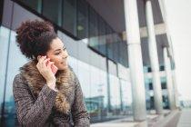 Lächelnde Frau telefoniert, während sie gegen das Gebäude sitzt — Stockfoto