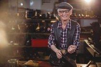 Улыбающийся старший сапожник чинит обувь в мастерской — стоковое фото