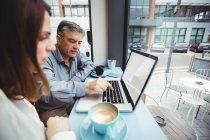 Homme et femme utilisant un ordinateur portable à la cafétéria — Photo de stock