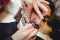 У перукарні людина обголила бороду бритвою. — стокове фото