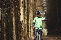 VTT vérifier le temps tout en chevauchant dans la forêt — Photo de stock