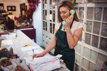 Жіночий флорист, перевірка рахунків-фактур під час розмови по телефону в квітковий магазин — стокове фото