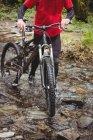 Низкий участок велосипедиста ходьба с велосипедом в ручье в лесу — стоковое фото