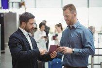 Les gens d'affaires vérifient leur passeport dans le terminal de l'aéroport — Photo de stock