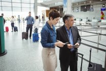 Business man and woman checking their passport in airport terminal — Stock Photo