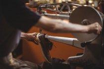 Руки шевця за допомогою швейні машини в майстерні — стокове фото