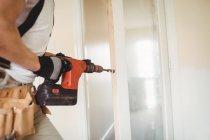 Imagem cortada de porta de madeira de perfuração de carpinteiro com máquina de perfuração em casa — Fotografia de Stock