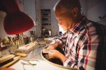 Внимательный ювелир, формирующий металл с плоскогубцами в мастерской — стоковое фото