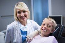 Retrato de dentista sorridente e paciente jovem na clínica odontológica — Fotografia de Stock