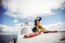 Pescador sentado en la cubierta y mirando hacia otro lado - foto de stock