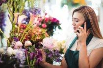 Fleuriste femme parlant sur téléphone portable tout en arrangeant des fleurs dans la boutique de fleurs — Photo de stock