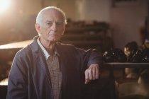 Senior calzolaio sorridente in piedi in officina — Foto stock