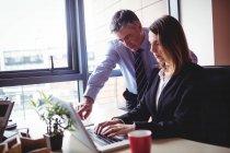 Бизнесмен обсуждает с коллегой за ноутбуком в офисе — стоковое фото