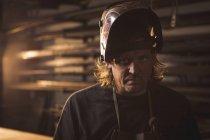 Portrait de forgeron en casque de protection à l'atelier — Photo de stock
