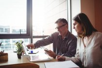 Людина, обговорюючи з колегою над ноутбук в офісі — стокове фото
