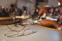 Крупный план очков на рабочем столе в мастерской — стоковое фото