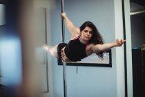 Attrayant Polonais danseur pratiquant pole dance dans le studio de fitness — Photo de stock