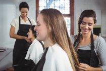 Coiffeurs souriants travaillant sur des clients au salon de coiffure — Photo de stock
