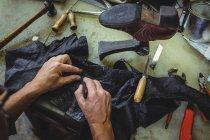 Mãos de sapateiro cortando um pedaço de material na oficina — Fotografia de Stock