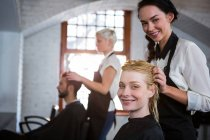 Portrait of smiling hair stylist massaging client hair in salon — Stock Photo