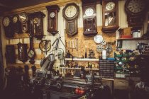 Antico laboratorio di orologiai con orologio riparazione di strumenti, attrezzature e orologi a muro — Foto stock