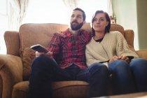 Пара, сидячи на дивані з пульта дистанційного керування під час перегляду телебачення у вітальні на дому — стокове фото