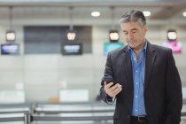 Uomo d'affari che utilizza il telefono cellulare nel terminal dell'aeroporto — Foto stock