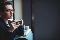 Empresária atenciosa segurando xícara de café no café — Fotografia de Stock