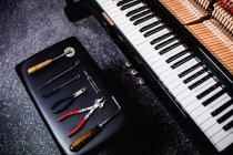 Primer plano de herramientas de reparación y teclado de piano viejo - foto de stock