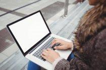 Обрезанное изображение женщины, печатающей на ноутбуке, сидящей на ступеньках — стоковое фото