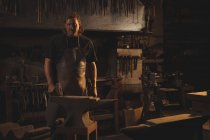 Portrait of blacksmith standing in workshop — Stock Photo