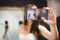 Женщина делает селфи, примеряя свадебное платье в студии — стоковое фото