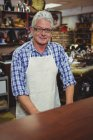 Confident smiling shoemaker standing in workshop — стокове фото
