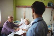 Coppia anziana che interagisce con il medico nel reparto ospedaliero — Foto stock