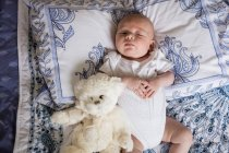 Vue surélevée de bébé dormant sur le lit avec ours en peluche à la maison — Photo de stock