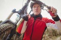Низким углом зрения горный байкер, перевозящих велосипедов — стоковое фото