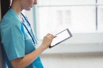 Krankenschwester mit digitalem Tablet an Krankenhauswand — Stockfoto