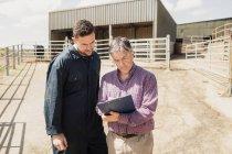 Працівник ферми і ветеринар, дивлячись у буфер обміну проти сарай на сонячний день — стокове фото
