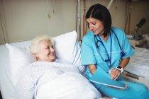 Медсестра, взаємодіючи з старший пацієнта у лікарні — стокове фото