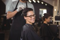 Hairdresser dyeing hair of client at salon — Stock Photo
