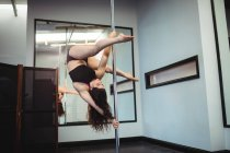 Attractive Pole dancer practicing pole dance in fitness studio — Stock Photo