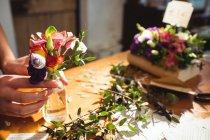 Крупный план женщины-флористки, раскладывающей цветы в бутылке в цветочном магазине — стоковое фото