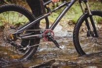 Низкая часть байкера ходьба с велосипедом в ручье — стоковое фото