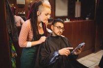 Клиент показывает цифровой планшет парикмахерше в парикмахерской — стоковое фото