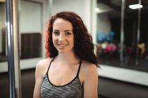 Portrait of pole dancer standing in fitness studio — Stock Photo