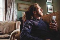 Молодой хипстер держит мобильный телефон на диване дома — стоковое фото