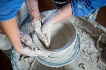 Oleiro macho de seção média ajudando oleiro fêmea na oficina de cerâmica — Fotografia de Stock