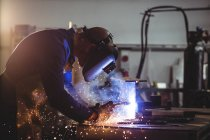 Male welder working on piece of metal in workshop — Stock Photo