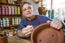 Pintura de alfarero masculino en maceta en taller de cerámica - foto de stock