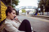 Belle femme parlant au téléphone à la gare — Photo de stock